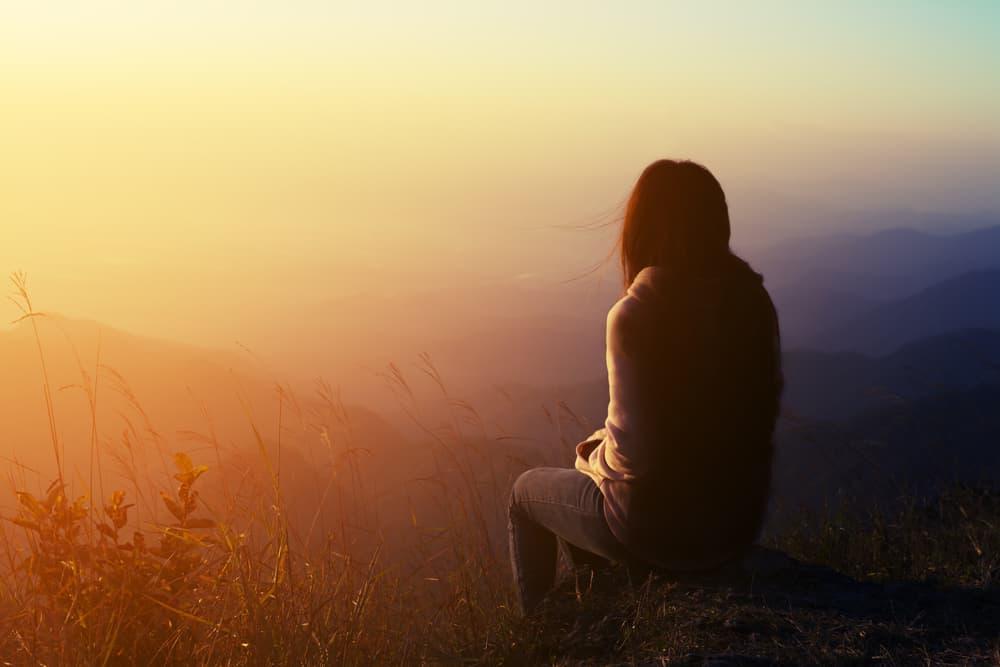 Die Frau sitzt alleine auf dem Stein