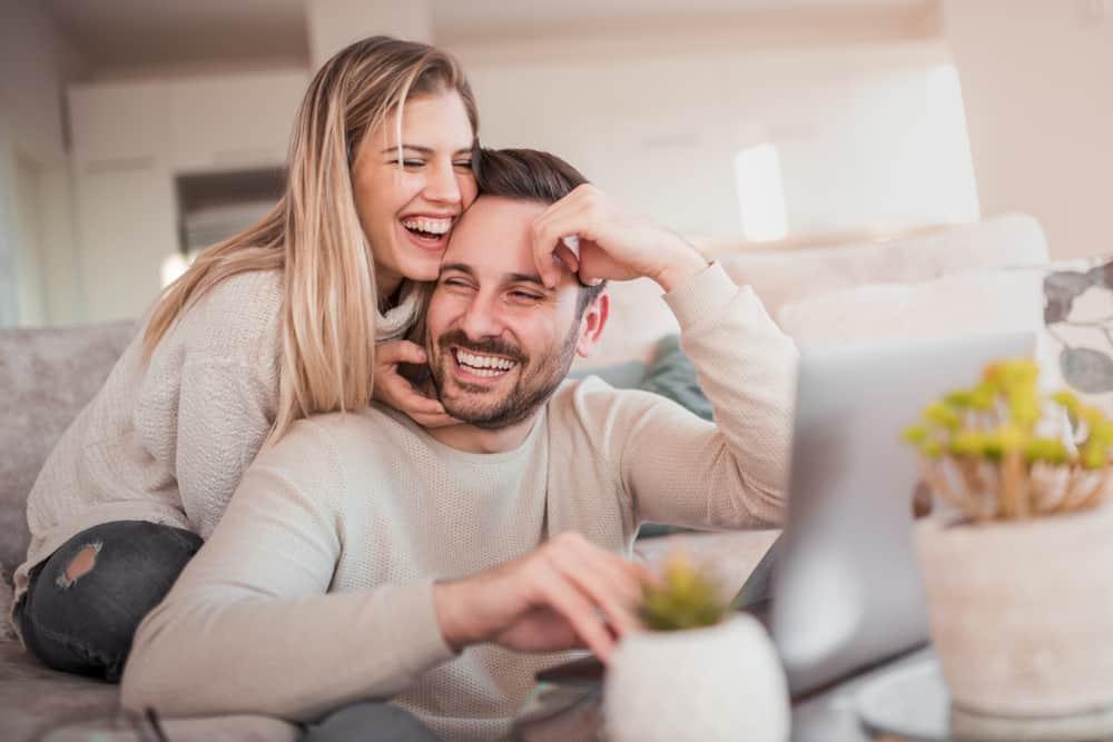 Die Frau umarmt den Mann und lacht, während er sich hinter dem Laptop befindet