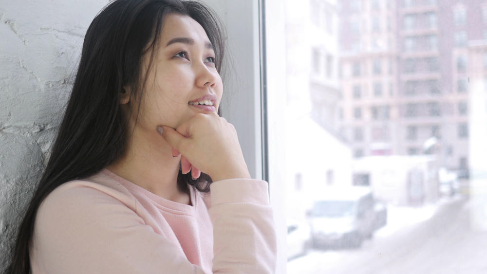 Die asiatische Frau mit einem Lächeln denkt nach und sitzt am Fenster