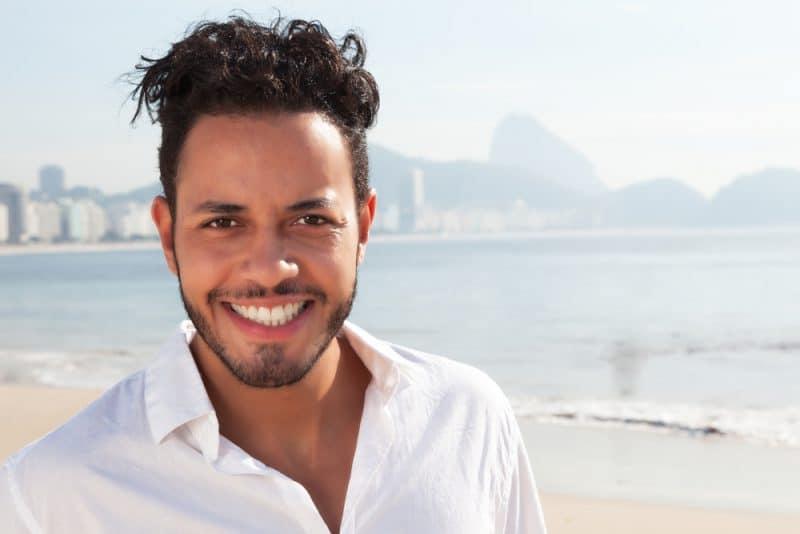 ein Porträt eines gutaussehenden Mannes in einem weißen Hemd am Strand