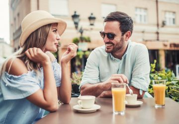 Eine Frau und ein Mann flirten über ein Café