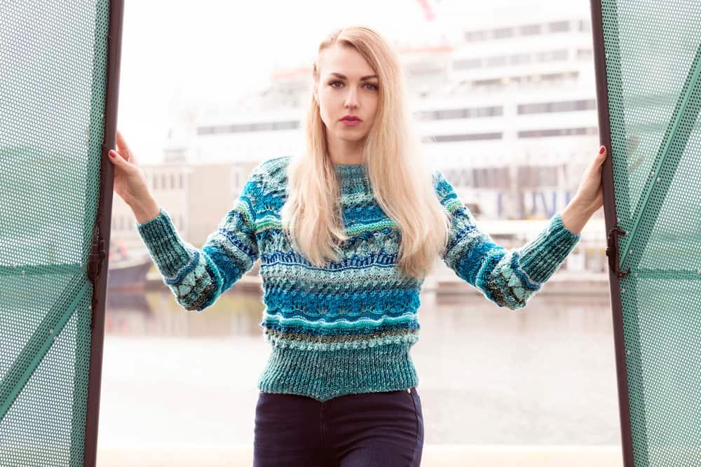 Draußen steht eine Blondine in einem bunten Pullover