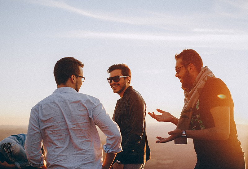 Drei Männer lachen, während sie zusammen im Freien stehen