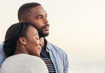 Der schwarze Mann und seine Frau stehen in einer Umarmung