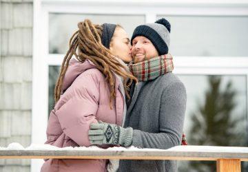 Eine Frau küsst einen Mann auf die Wange