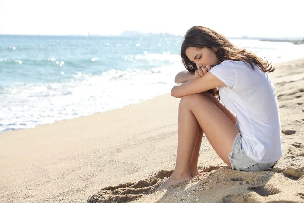 Ein Mädchen in kurzen Hosen sitzt leider am Strand