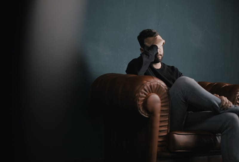 Ein Mann berührte seinen Kopf, während er auf dem Sofa saß und sich verwirrt fühlte