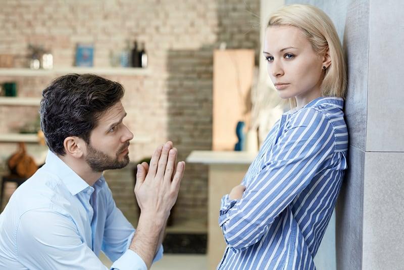 Ein Mann, der seine Freundin auf gebeugten Knien um Vergebung bittet.