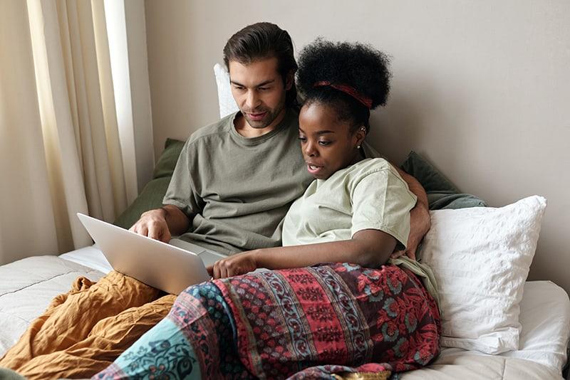 Ein Mann bittet eine Frau um Rat, während beide einen Laptop im Bett suchen
