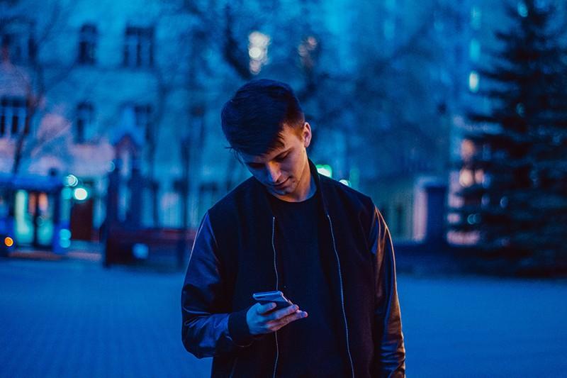 Ein Mann, der auf dem Weg steht und nachts ein Smartphone benutzt