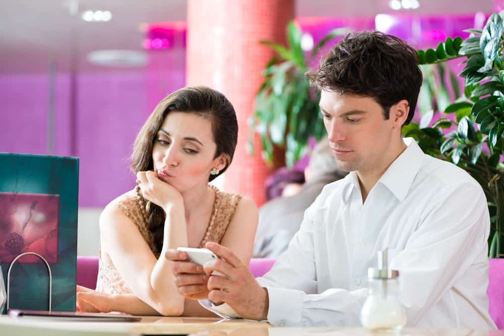 Ein Mann, der ein Handy benutzt, sitzt mit einer Frau in einem Café
