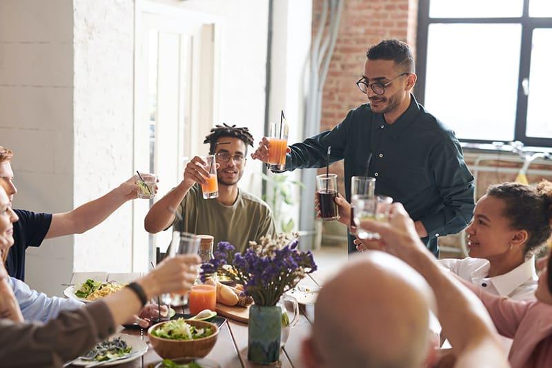 Ein Mann, der während eines Mittagessens mit einer Gruppe von Freunden einen Toast macht