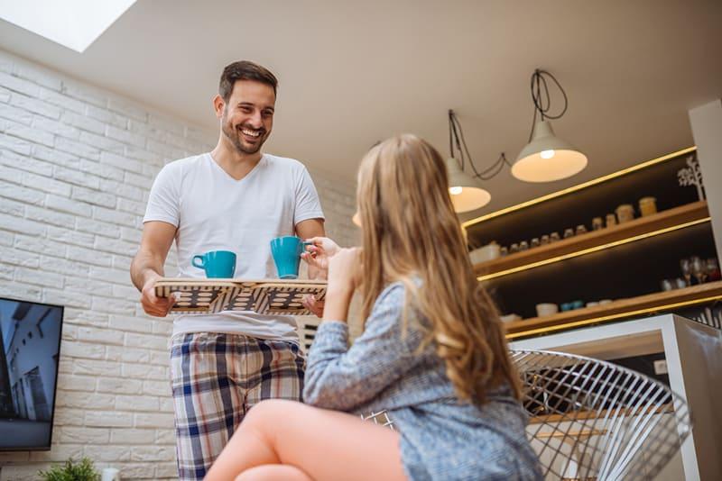 Ein Mann bringt seiner Freundin Kaffee, die auf dem Sessel sitzt