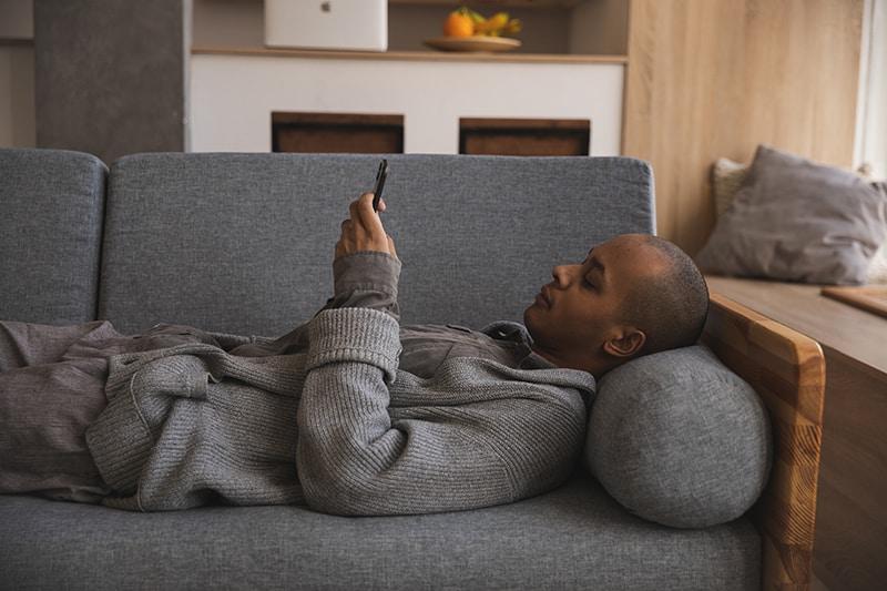 Ein Mann, der sich auf der Couch entspannt und ein Smartphone benutzt