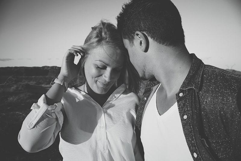 Ein Mann flüstert einer schüchternen Frau ins Ohr, während er mit ihr flirtet