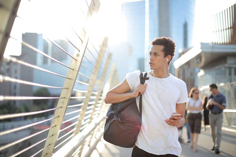 Ein Mann hält ein Smartphone und schaut zur Seite, während er auf der Brücke geht