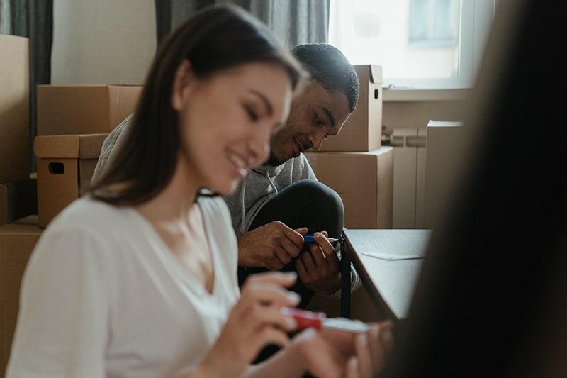 Ein Mann hilft einer Frau beim Zusammenbau des Couchtischs in ihrer neuen Wohnung