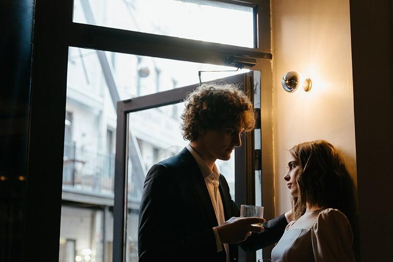 Ein Mann in einem Anzug, der mit einer ernsten Frau flirtet, die sich an die Wand lehnt