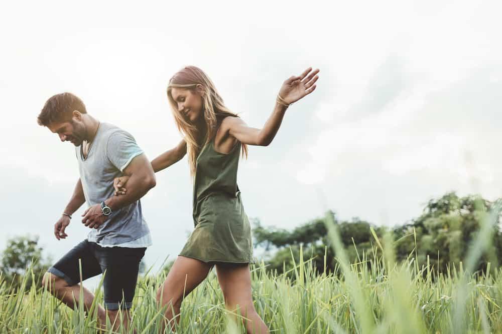 Ein Mann in einem weißen T-Shirt und eine Frau in einem kurzen Kleid gehen auf dem Rasen spazieren