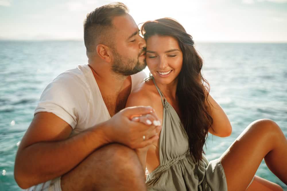Ein Mann küsst eine Frau auf den Kopf, während er auf einer Yacht sitzt und segelt
