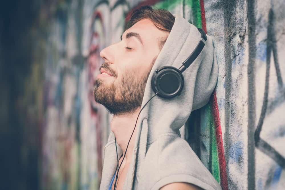 Ein Mann mit Bart, der an eine Wand gelehnt ist, hört Musik über Kopfhörer