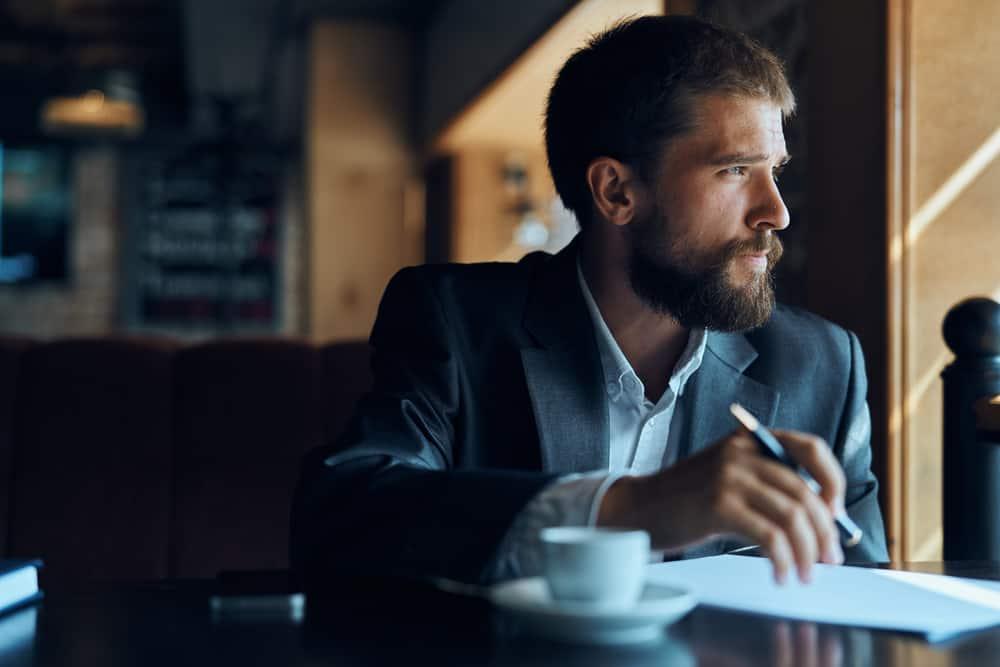 Ein Mann mit Bart und Bleistift in der Hand sitzt in einem Café und denkt nach