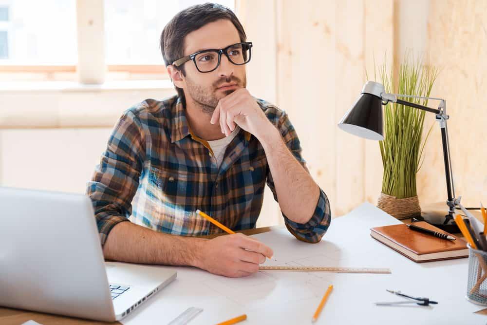 Ein Mann mit Brille in kariertem Hemd sitzt und zeichnet