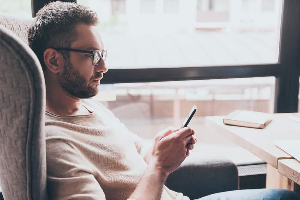 Ein Mann mit Brille sitzt in einem Sessel und benutzt ein Smartphone