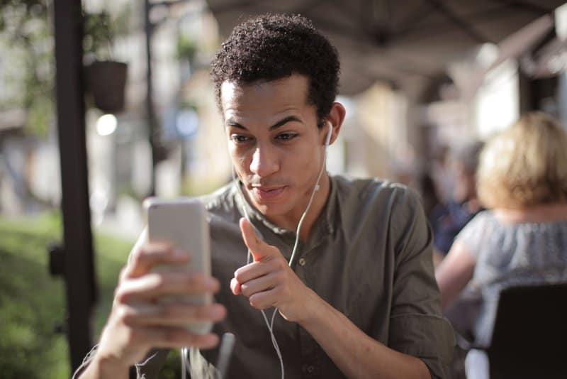 Ein Mann mit Kopfhörern in den Ohren spricht über ein Smartphone mit jemandem