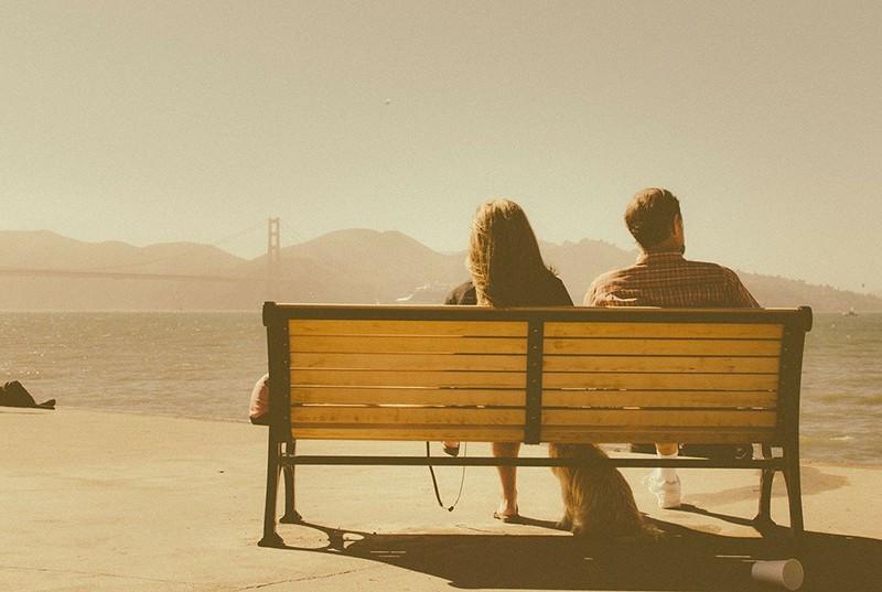 Ein Mann schaut zur Seite, während er auf der Bank neben einer Frau in der Nähe eines Gewässers sitzt