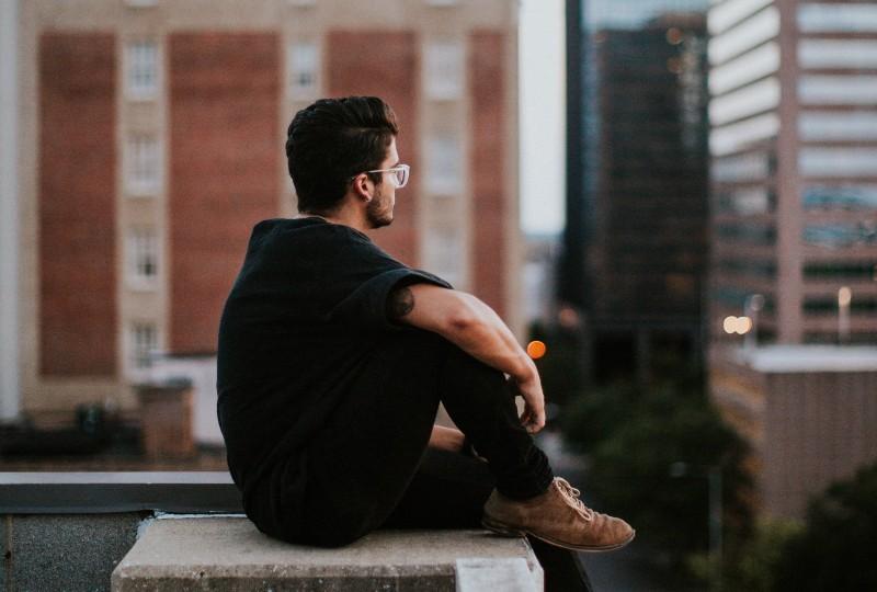 Ein Mann sitzt allein oben im Gebäude