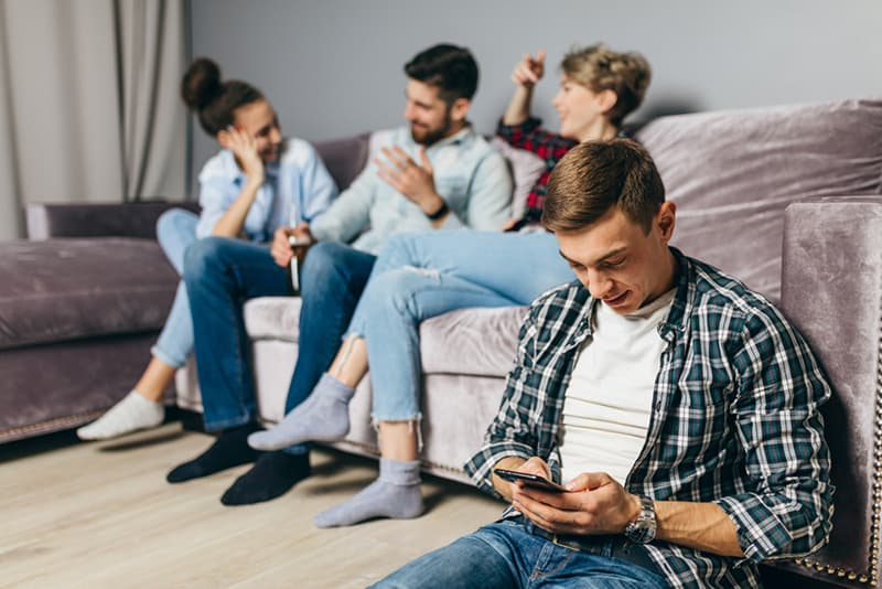 Ein Mann sitzt auf dem Boden und benutzt ein Smartphone, während ihre Freunde reden und auf der Couch sitzen