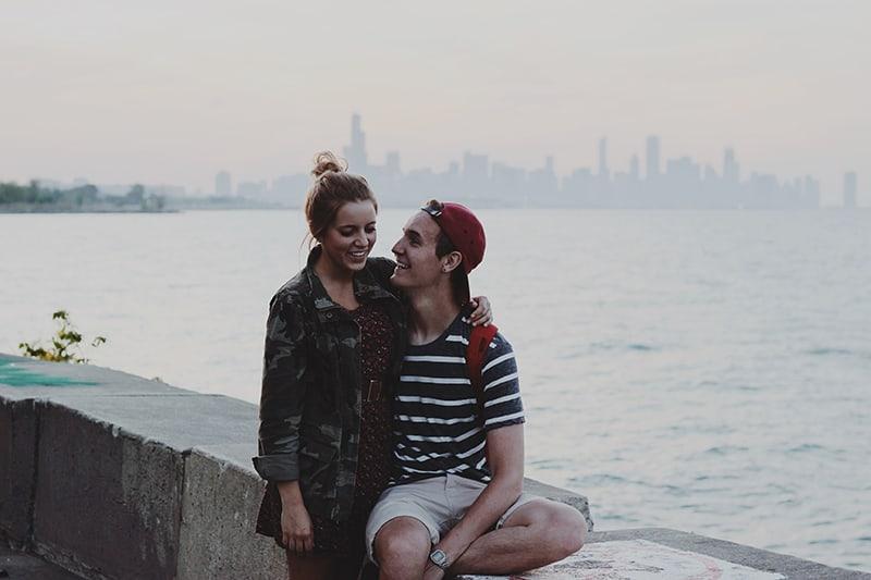 Ein Mann sitzt auf der Betonwand und umarmt eine Frau, die während eines Dates in seiner Nähe steht