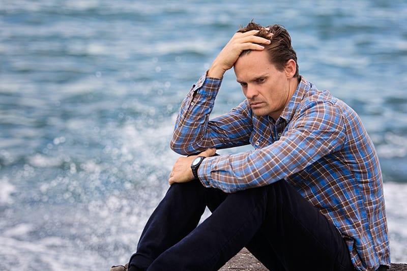 Ein Mann sitzt in der Nähe eines Gewässers und berührt beim Nachdenken seinen Kopf