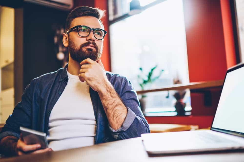 Ein Mann sitzt mit einem Handy in der Hand und denkt nach