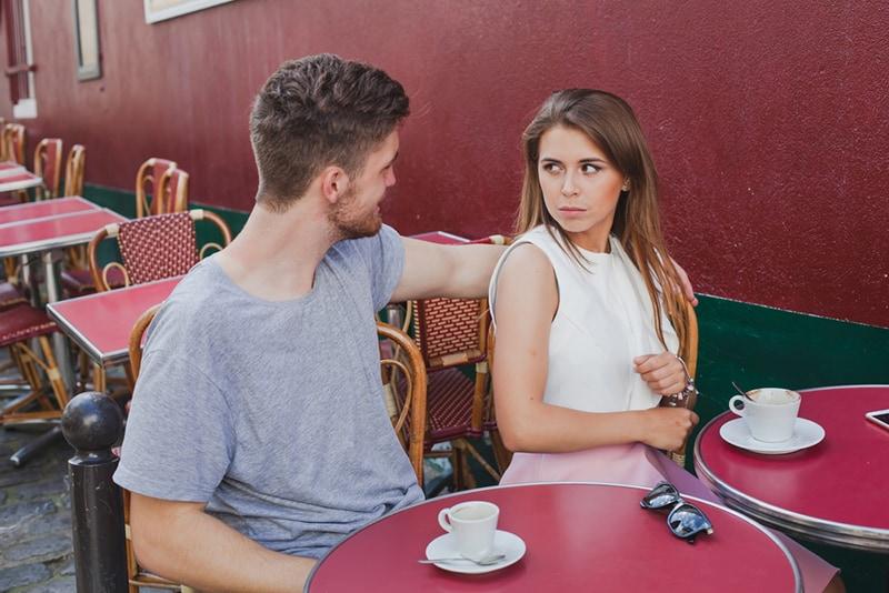 Ein Mann, der mit einem Mädchen spricht, das ihn ablehnt, während er im Caffe sitzt