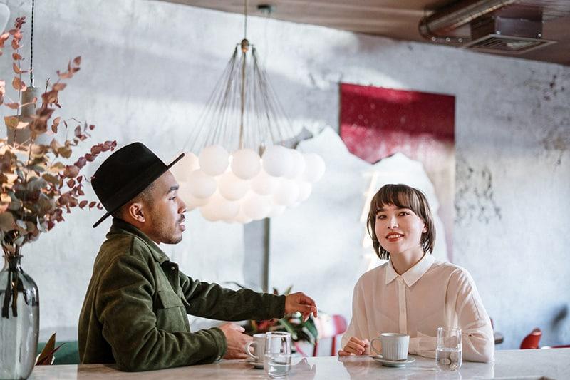 Ein Mann spricht mit einer Frau, die bei einem Date zur Seite schaut