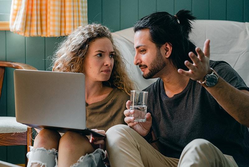 Ein Mann spricht mit einer verwirrten Frau, während er auf dem Boden sitzt