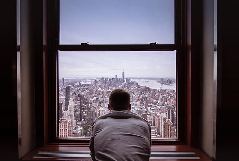 Ein Mann stand allein in der Nähe des Fensters mit Blick auf die Stadt