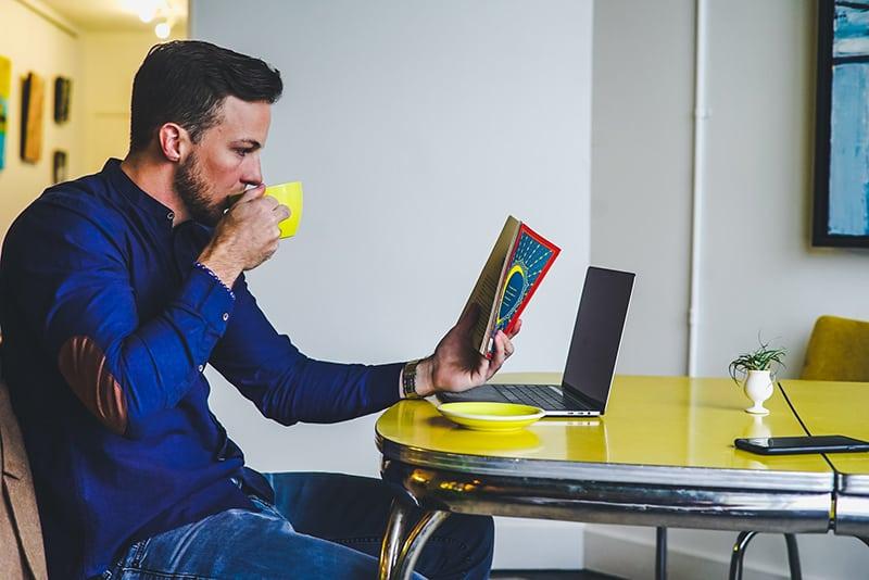Ein Mann trinkt Kaffee, während er ein Buch liest, während er mit Laptop und Smartphone am Tisch sitzt