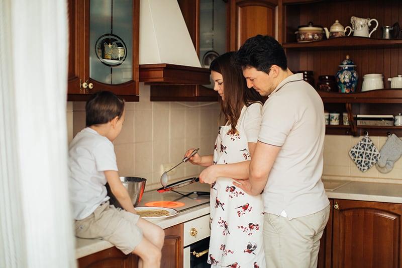 Ein Mann umarmt eine Frau, die das Essen zubereitet, während ihr Sohn auf der Küchentheke sitzt
