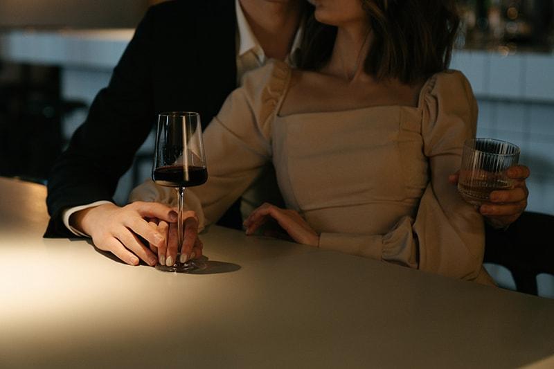 Ein Mann umarmt eine Frau, die das Glas Wein berührt, während sie an der Bartheke sitzt