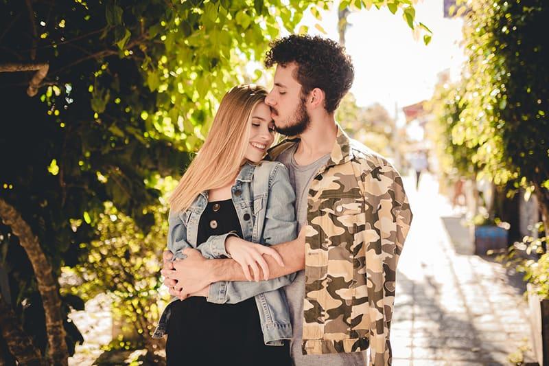 Ein Mann umarmte eine Frau von hinten und küsste sie auf die Stirn