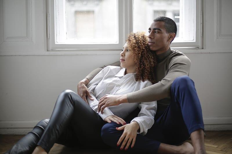 Ein Mann umarmt eine Frau, während er auf dem Boden im Haus sitzt