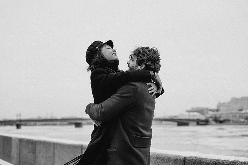 Ein Mann umarmte und hob seine Frau in die Nähe des Gewässers