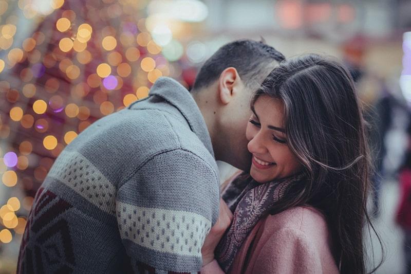 Ein Mann umarmt und küsst eine lächelnde Frau auf die Wange
