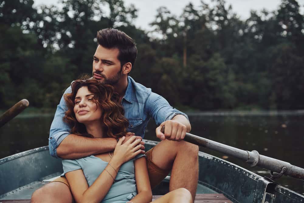 Ein Mann und eine Frau fahren ein Boot, während ein Mann sie umarmt