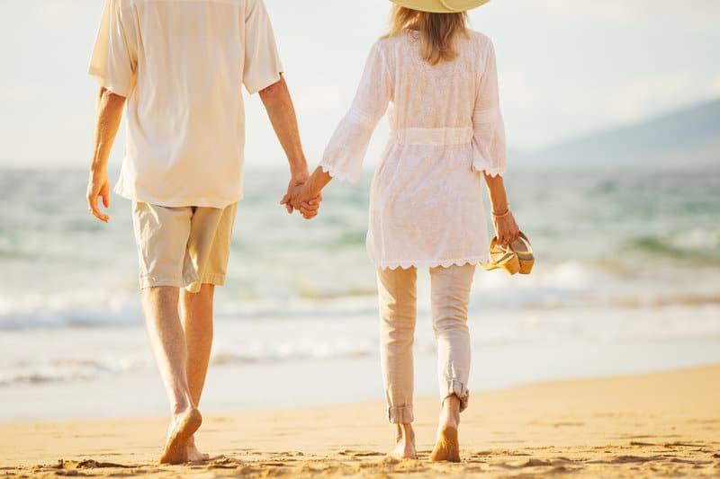 Ein Mann und eine Frau gehen Händchen haltend am Strand entlang
