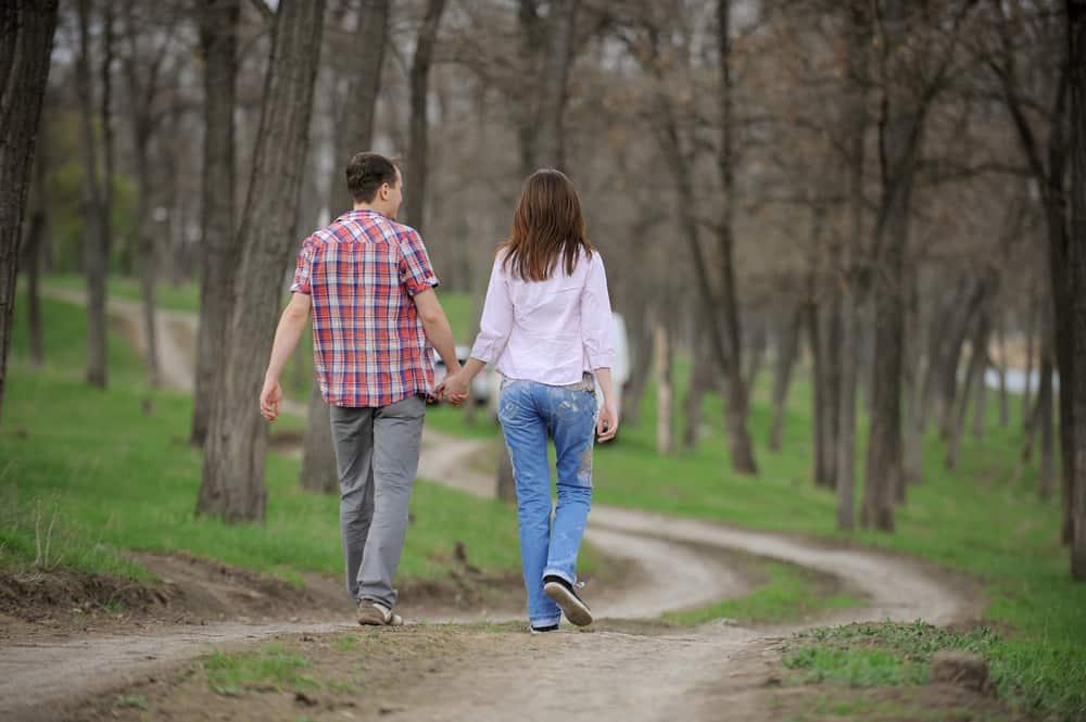 Ein Mann und eine Frau gehen Händchen haltend durch den Wald