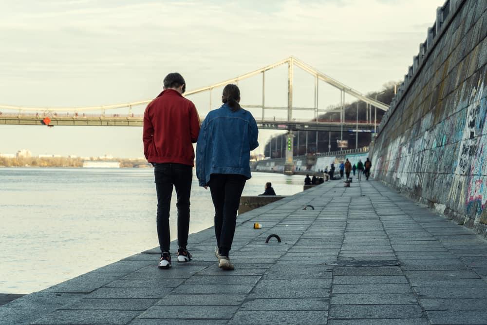 Ein Mann und eine Frau gehen am Ufer entlang